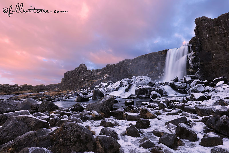 Winter waterfall against dramatic sky in Thingvellir National Park in Iceland