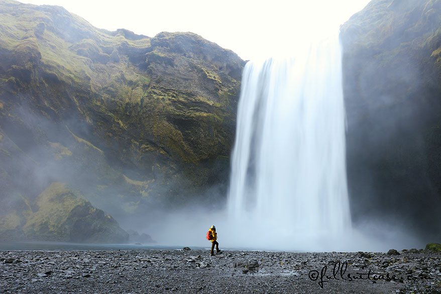 Hiker standing at a foot of a majestic Skogafoss Waterfall in Southern Iceland