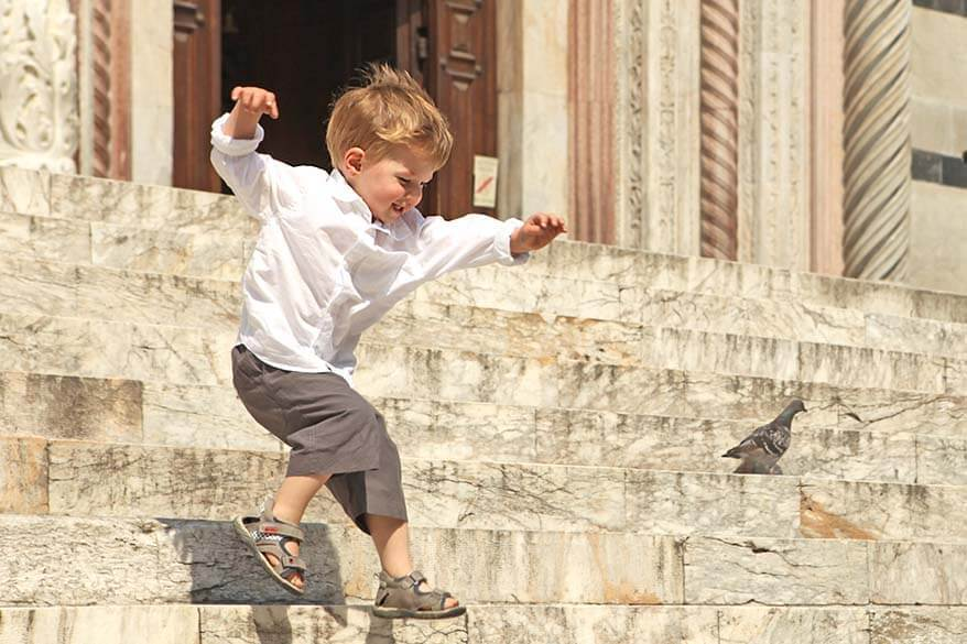 Child playing in an Italian city in summer