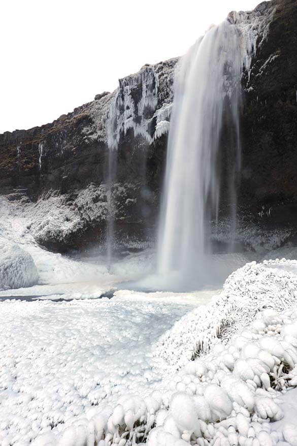 Partially frozen Seljalandsfoss waterfall in Iceland in winter