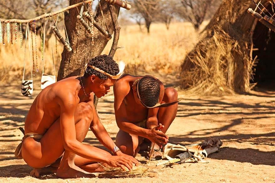 Bushmen tribe men making fire the traditional way