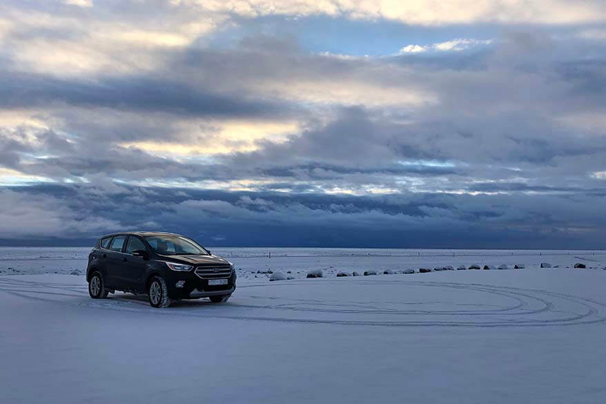 4WD vehicle at an empty parking lot covered with snow - driving Iceland's South Coast in winter