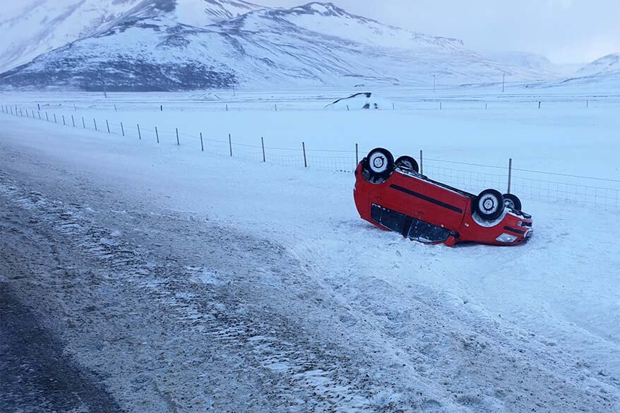 Car accident in Iceland in winter - red car upside down next to an icy road