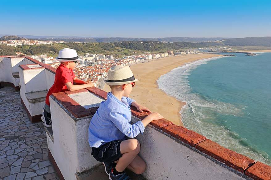 Kids looking at the view of Miradouro do Suberco in O Sitio district of Nazare Portugal