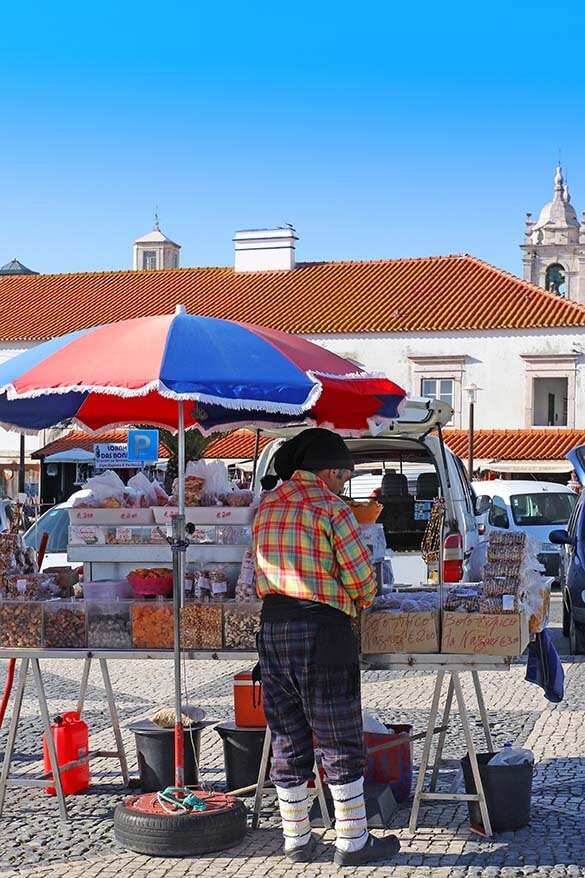 Local salesman in traditional clothing at the market in O Sitio district in Nazare Portugal