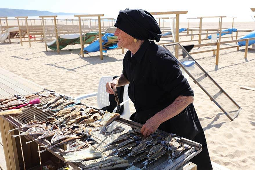Local women in traditional black clothing selling dried fish in Nazare Portugal