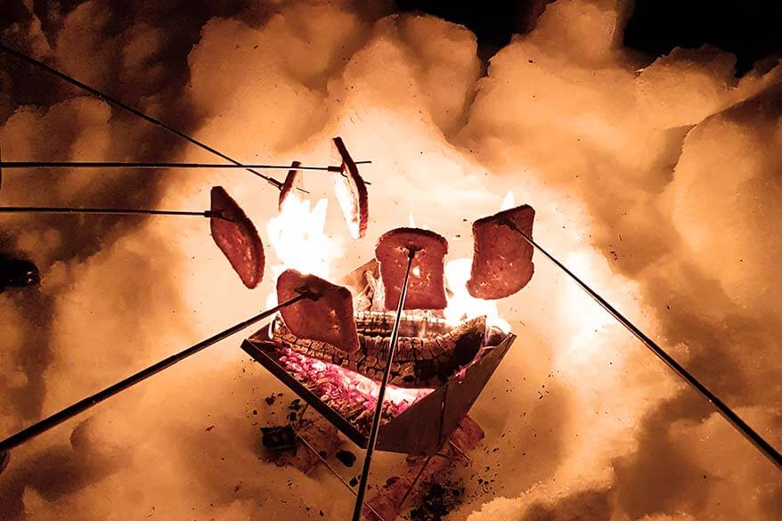 Toasting bread by the bonfire on a small group northern lights tour in Norway in winter