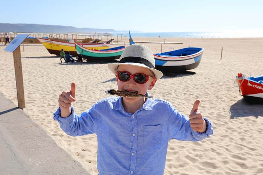 Boy eating dry fish in Nazare Portugal