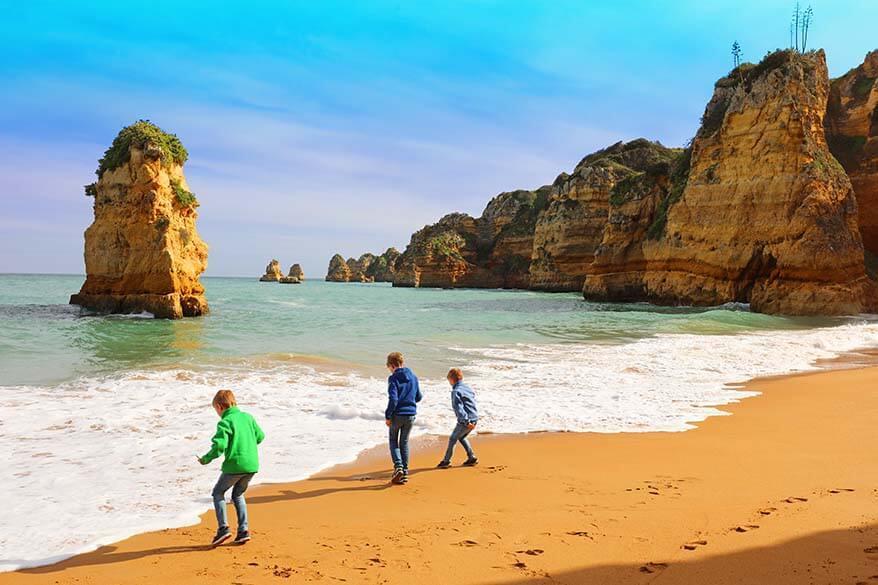 Kids playing on the beautiful Praia de Dona Ana beach near Lagos in Algarve, Portugal