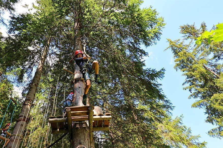 Kids ziplining in Bichlbach kletterwald - adventure park in Tiroler Zugspitz arena in Tyrol Austria