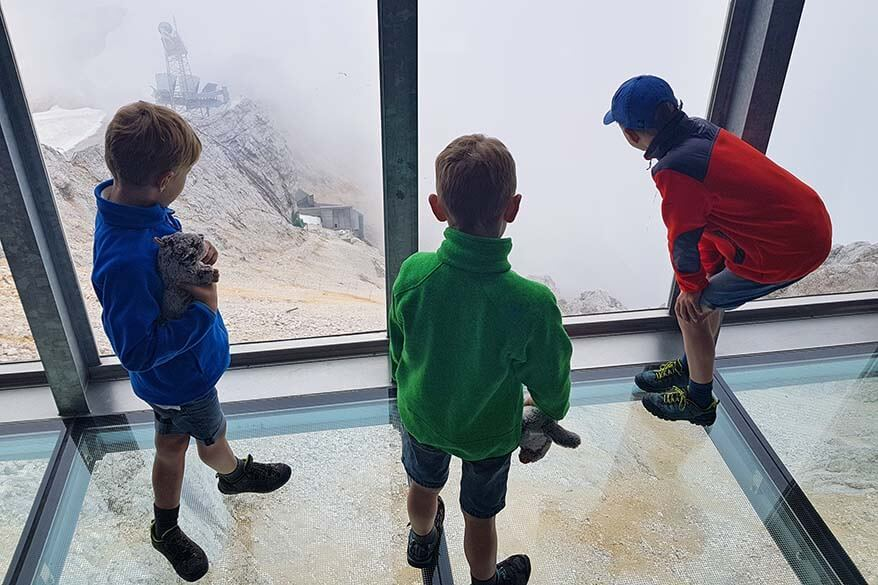 Kids standing on a glass floor overlooking the steep moutain at Zugspitze in Austrian Tirol