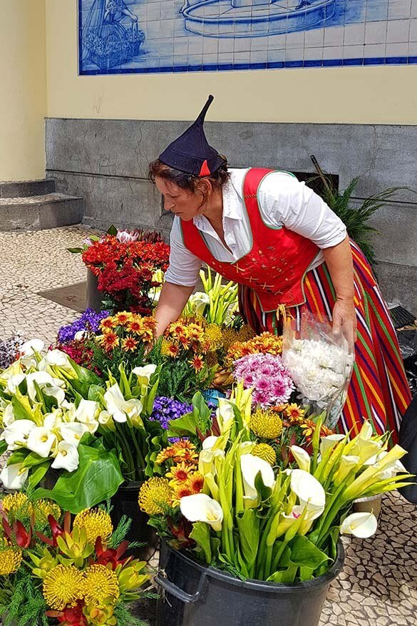 A woman in traditional Madeira folk clothing selling exotic flowers at Mercado dos Lavradores market in Funchal