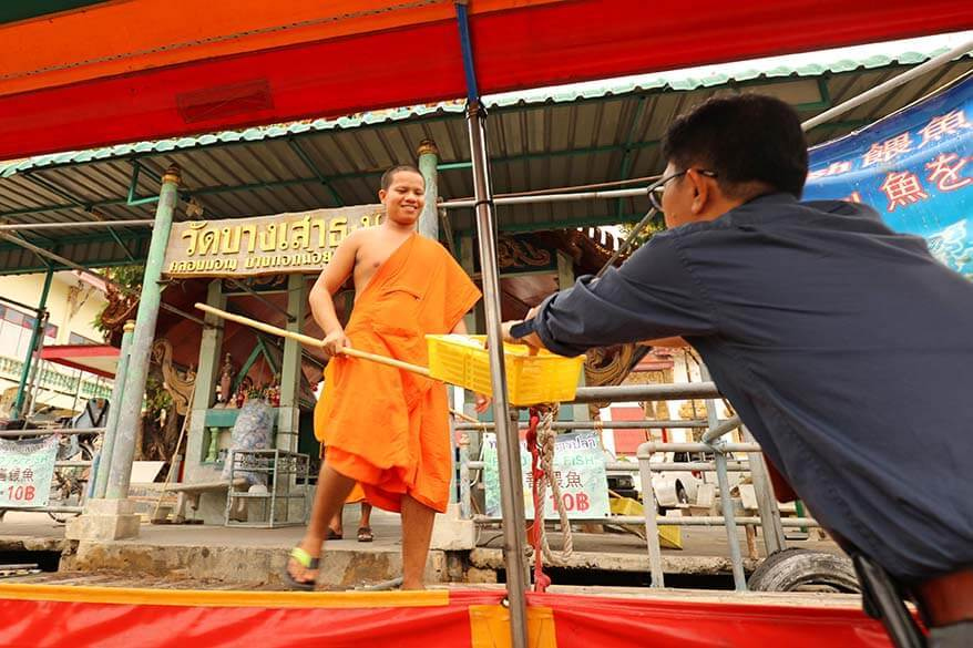 Buying bread for the fish from Buddhist monks at Wat Chinorot temple along Bangkok's canals