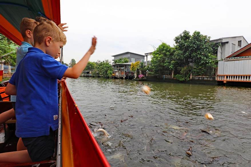Kids feeding fish during Bangkok canal tour in Thonburi area