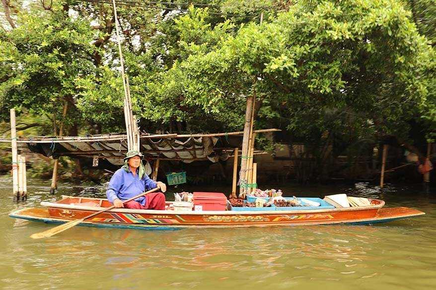 Vendor selling souvenirs from his wooden boat in Bangkok