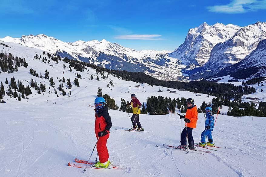 Family skiing with amazing views of Jungfrau Region ski area in winter - Switzerland