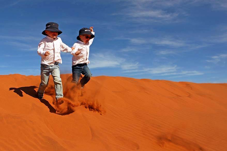 Kids running down the sand dunes in Sossusvlei in Namibia