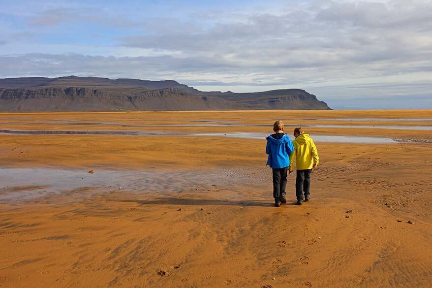 Kids walking on Raudisandur beach in Iceland