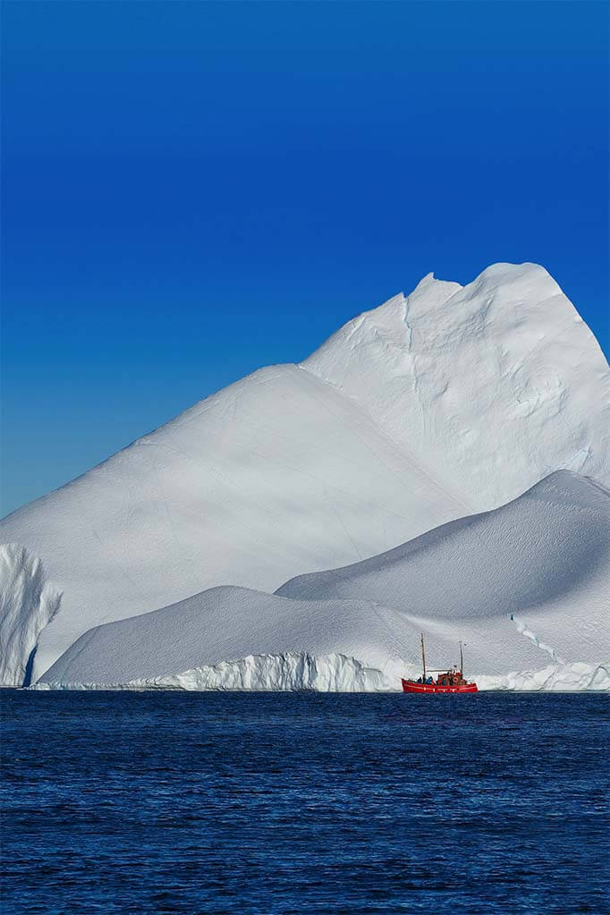 Small boat in front of a huge iceberg in Greenland