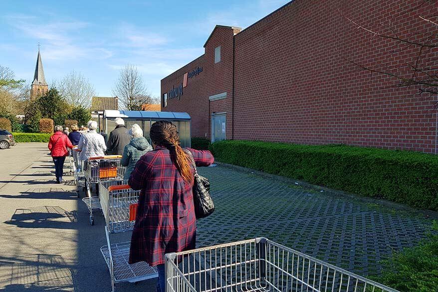 Row of people waiting to enter a supermarket - coronavirus in Belgium