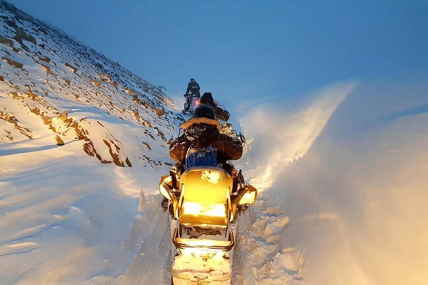 Snowmobiles driving through a canyon in Svalbard