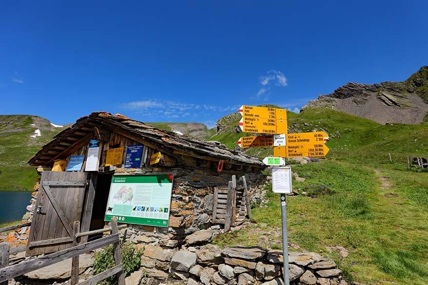 Mountain hut and hiking trail informational signs at Bachalpsee in Switzerland