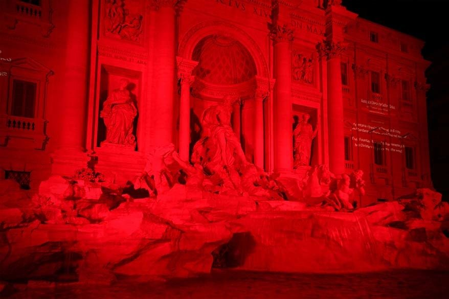 Trevi Fountain lit in red in the dark