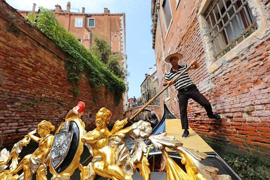 Gondolier steering Venetian gondola through a very narrow canal