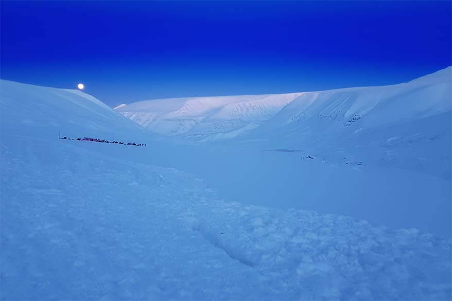 Blue light and winter scenery during the dog sledding and ice caves tour in Svalbard