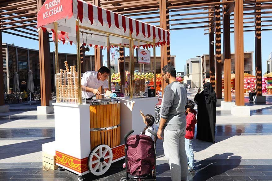 Family at Turkish ice cream stand on The Walk in Dubai