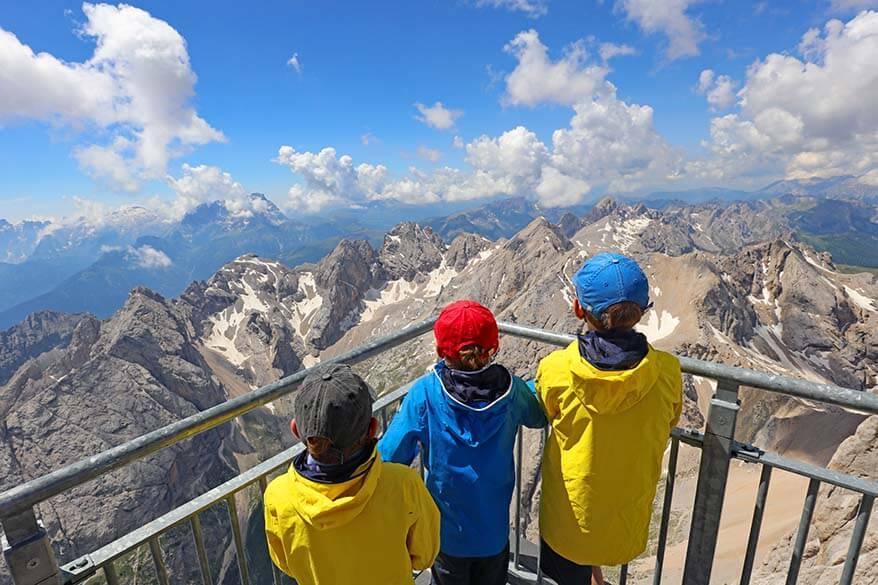 Kids admiring mountain scenery at Marmolada in Italian Dolomites