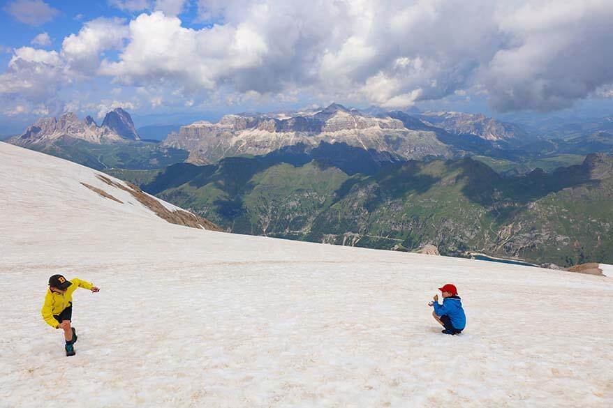 Kids playing on the snow on Marmolada glacier in summer