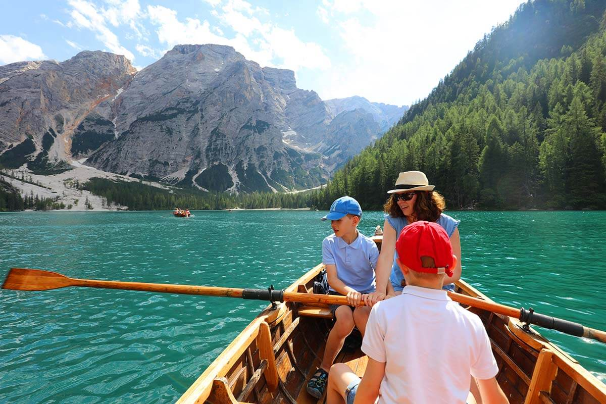 Family rowing a boat on Pragser Wildsee in the Dolomites Italy