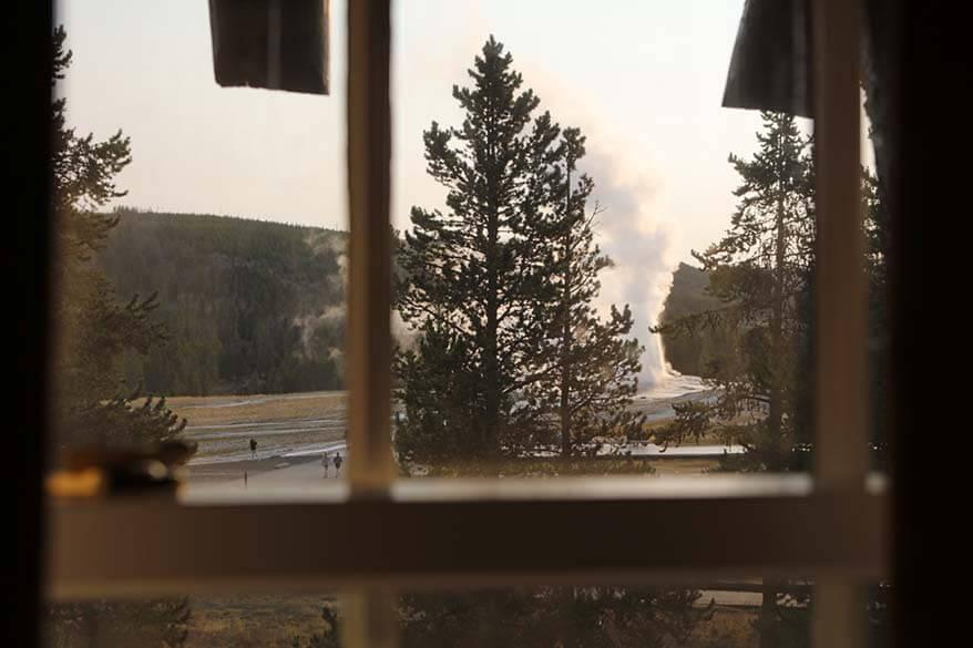 View on Old Faithful Geyser through a room window at the Old Faithful Inn hotel in Yellowstone National Park