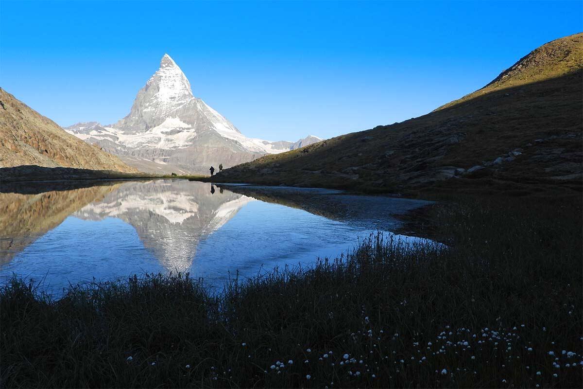 Hikers and Matterhorn reflections at Riffelsee Lake in Zermatt Switzerland